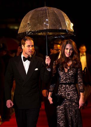 Σωστός ιππότης ο πρίγκιπας Γουίλιαμ προστατεύει τη σύζυγό του, Κέιτ, από τη βροχή καθώς προσέρχονται στην πρεμιέρα της ταινίας  War Horse  την παραμονή των 30ών γενεθλίων της.