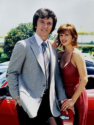 Η Πρίνσιπαλ με τον τηλεοπτικό σύζυγό της, Ρόμπι (Πάτρικ Ντάφι) σε σκηνή από το  Ντάλας .