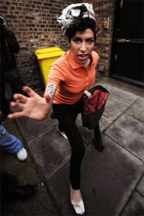 Η Έιμι Γουάινχαουζ, επιτίθεται στους φωτογράφους την ώρα που βγαίνει από το σπίτι της.