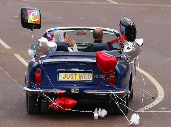 Οι νεόνυμφοι αποχωρούν από την εκκλησία για το παλάτι του Μπάκιγχαμ μέσα σε μια συλλεκτική Aston Martin.