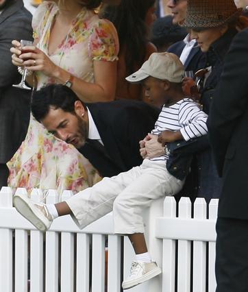 Η Μαντόνα κρατάει τον γιο της Ντέιβιντ Μπάντα που δείχνει τα παπουτσια του στον σχεδιαστή Μαρκ Τζέικομπς.
