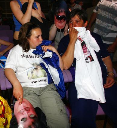 Θαυμαστές της Σούζαν που φορούσαν μάσκες με τη μορφή της, για να την υποστηρίξουν, ακούν απογοητευμένοι το αποτέλεσμα.