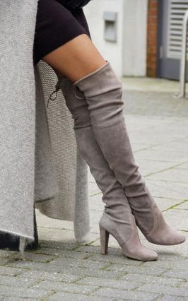 Εντυπωσιακές μπότες που φτάνουν πάνω από το γόνατο με μεσαίου μεγέθους τακούνι είναι η ιδανική επιλογή για το μίνι μαύρο και σέξι φόρεμά σου.
