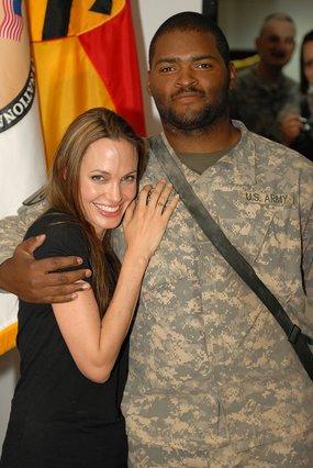 Πασιχαρής αμερικανός στρατιώτης αγκαλιάζει προστατευτικά την  Αντζελίνα Τζολί κατά την επίσκεψή της στα στρατεύματα της Βαγδάτης.