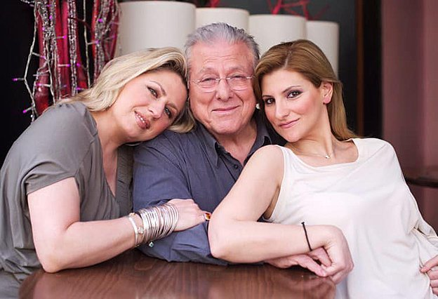 <p>Ο Κώστας Βουτσάς με τις κόρες του Σάντρα (αριστερά) και Θεοδώρα όπως τους είχε απαθανατίσει με τον φακό της παλιότερα η Ολυμπία Κρασαγάκη. Τη φωτογραφία αυτή μοιράστηκε σήμερα στο Facebook η ίδια η